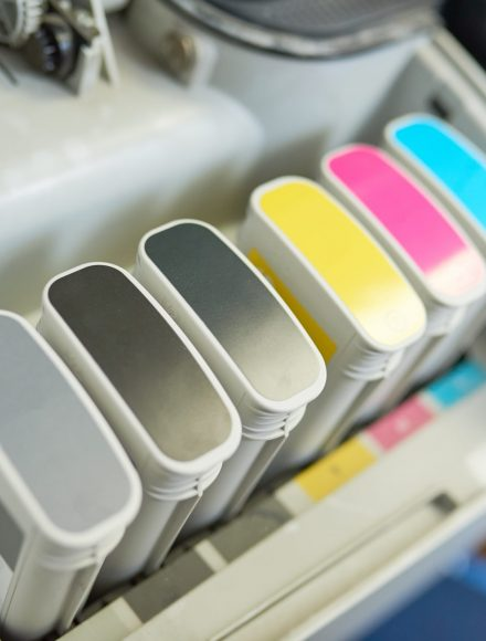 Close up of plotter ink tanks with color marks in printing shop or publishing agency